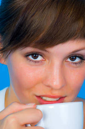 Portrait a young beautiful girl with Cappuccino in front of a blue background Stock Photo - 8139291