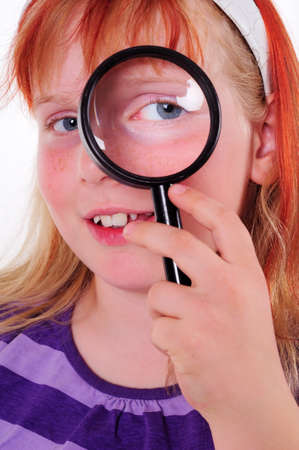 Portrait of a young girl playing with a magnifying glass Stock Photo - 8762944