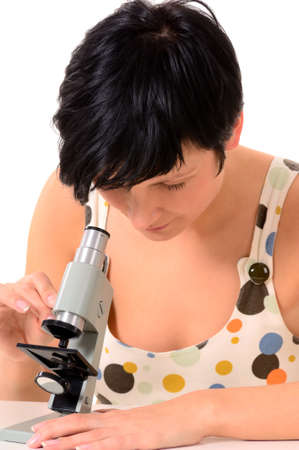 Young female student working with a microscope photo