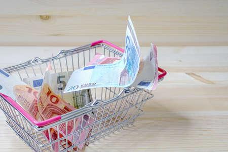 Moneybox, euro banknote in shopping basket