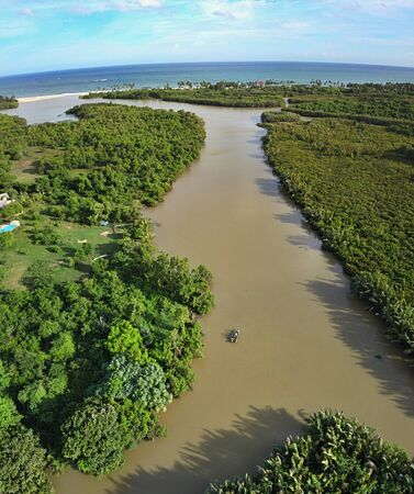 Muddy river and mangrove forest with boat