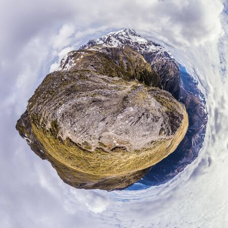 Aerial tiny planet on top of mountain with snow caps on a horizon and clouds on sky