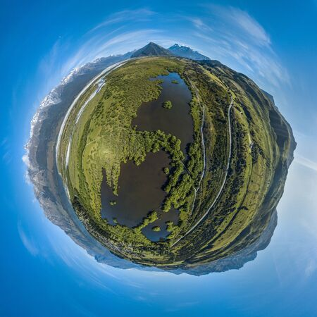 Aerial tiny planet of the swamp and mountains on horizon during sunny day