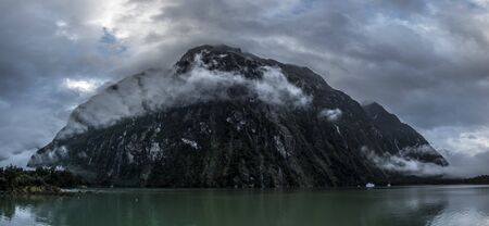 Steep and dark cliffs in clouds coming from water Stok Fotoğraf