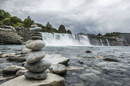 Stone mound with river and waterfall on background 版權商用圖片