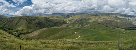 Green grasslands hills with white clouds wide panorama