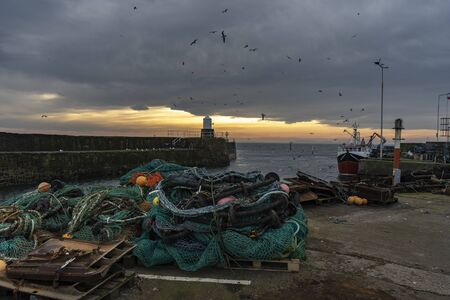 Historical harbor with an old traditional fishing nets boat and lighthouse during cloudy sunset Stock fotó