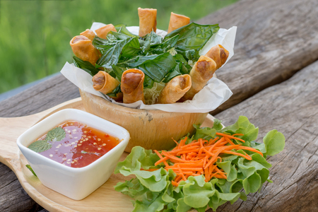 Thai food - Fried spring rolls with crispy noodle served with sweet and spicy sauce on the wooden plate Imagens