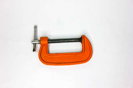 C-clamp in a horizontal close up photography. Image of orange tools isolated on white background. Banco de Imagens
