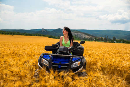 Sexy Girl is Riding a Quad Bike in the field with yellow plants. Footage. Rides ATV quad auto. Adventures of off-road on beautiful place with women model.