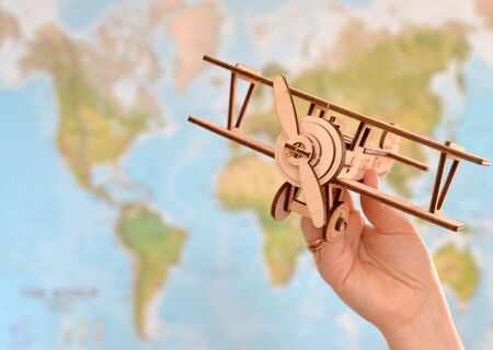 close up photo of womans hand holding toy airplane against map of world. empty space you can place your text or information.