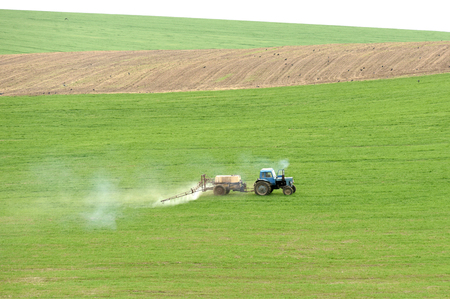 tractor spraying the chemicals on the green field.tractor sprinkling pesticides against bugs on agricultural field Stock Photo
