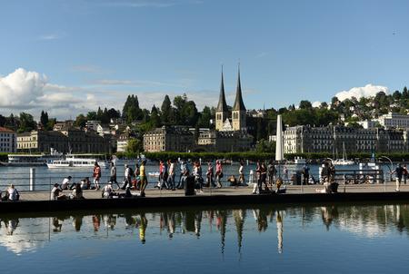Luzern, Zwitserland - 4 juni, 2017: Cityscape van Luzerne met mensen op dijkmeer Luzerne en kerk van St. Leodegar bij de achtergrond, Zwitserland. Redactioneel
