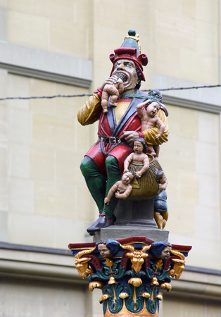 A fountain topped by a sculpture of an ogre eating children in Bern, Switzerland Stock Photo