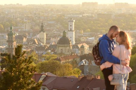 Lviv, Ukraine - April 10, 2017: A young couple tourists  with Lviv panorama on the backgrounds in evening time.