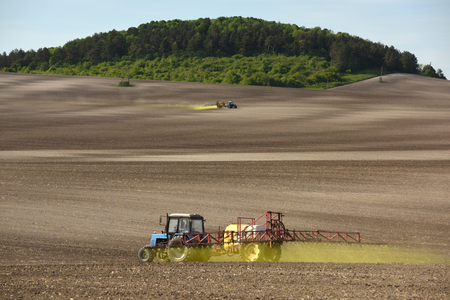 tractor spraying the chemicals on the field. tractor sprinkling pesticides against bugs on agricultural field. Stock Photo