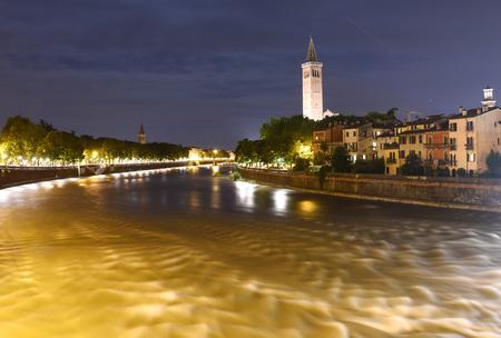 Verona cityscape at night with Sant Anastasia Church (Campanile Sant Anastasia) and Adige River, Verona, Italy