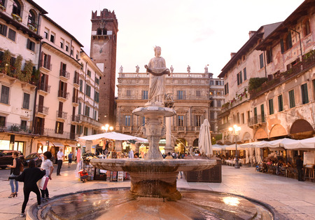 Verona, Italy June 06, 2017: Fountain statue of Madonna Verona (Fountain of our Lady Verona) with Palazzo Maffei and Gardello tower at the background on Piazza delle Erbe  in Verona, Italy.