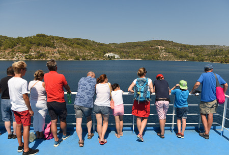 Korcula, Croatia - August 2017: People look at the island Korcula from the ferry. Stock Photo - 86404818
