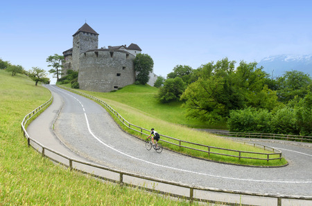 A bicyclist near Castle in Vaduz, Liechtenstein. This castle is the palace and official residence of the Prince of Liechtenstein