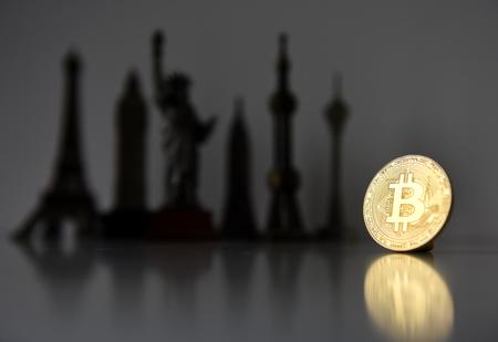 Bitcoin concept, cryptocurrencies. World economy concept. Golden coin bitcoin and souvenir from around the world.