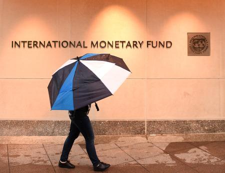Washington, DC - June 04, 2018: Pedestrian with an umbrella near International Monetary Fund, IMF Headquarters 2 Building (HQ2) in DC. Editorial