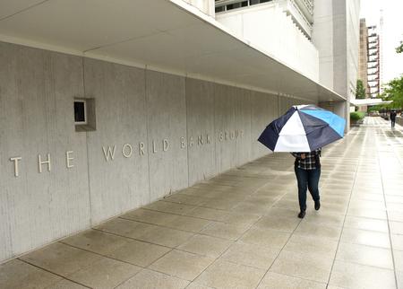 Washington, DC - June 04, 2018: Pedestrian with an umbrella near The World Bank main Building in Washington.