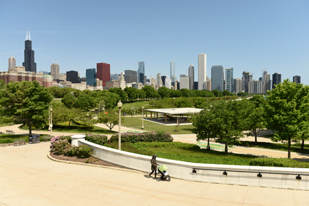 Chicago, USA - June 05, 2018: Woman with a baby carriage in The Great Ivy Lawn at The Field Museum Park and Chicago skyscrapers at the backgroun.