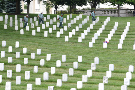 Washington, DC - June 01, 2018: Workers mow a grass on Arlington National Cemetery.