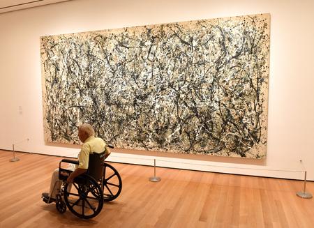 New York, Verenigde Staten - 25 mei 2018: Een man in rolstoel kijkt naar het schilderij van Jackson Pollock in Museum of Modern Art in New York City.