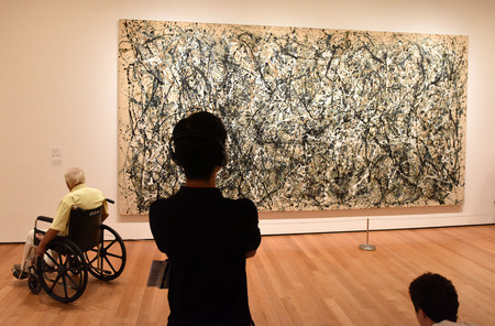 New York, USA - May 25, 2018: A visitors looks at the Jackson Pollock painting in Museum of Modern Art in New York City.