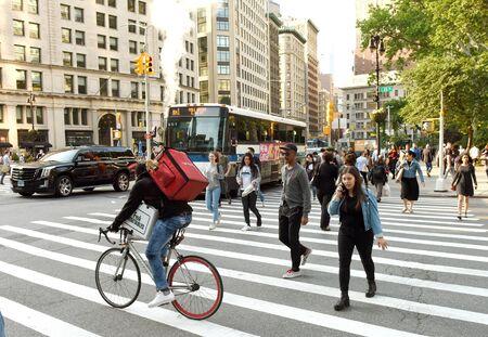 New York, USA - June 7, 2018: People walking on zebra crossings near the Flatiron Plaza in New York.