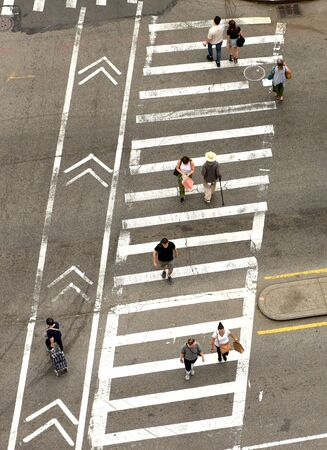 New York, USA - June 9, 2018: People walking on zebra crossings in New York. Looking down from skyscraper on the busy streets in New York. Sajtókép