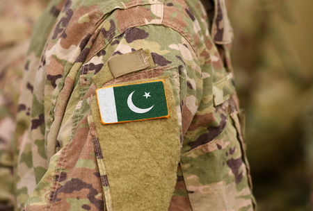 Pakistanische Flagge auf Soldatenarm. Pakistanische Truppen (Collage)