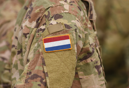 Flag of Netherlands on soldiers arm (collage). Banco de Imagens