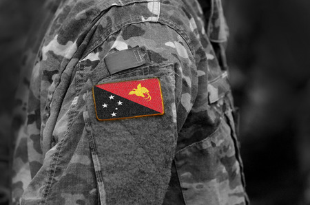 Flag of Papua New Guinea on soldiers arm. Flag of Papua New Guinea on military uniforms (collage).