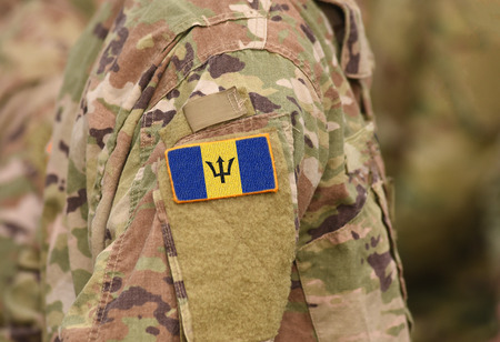 Flag of Barbados on soldiers arm. Flag of Barbados on military uniforms (collage). Reklamní fotografie