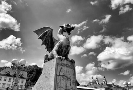 The Dragon statues at the Dragon Bridge and Cathedral of St. Nicholas at the background in center of Ljubljana, Slovenia
