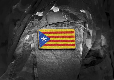 Flag of Catalonia (Estelada Blava) on military uniform. Estelada Blava flag is an unofficial flag typically flown by Catalan independence supporters. Collage. 스톡 콘텐츠