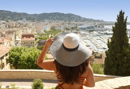 Woman in a hat looks at the cityscape of Cannes.