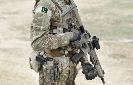 Soldier with machine gun and flag of Pakistan on military uniform. Collage.