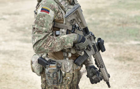 Soldier with assault rifle and flag of Venezuela on military uniform. Collage. Standard-Bild