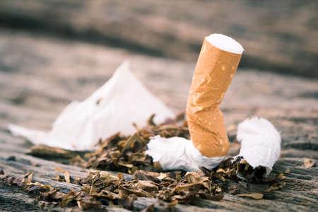 Zigarette auf einem Holztisch. Licht und Farbeffekt.