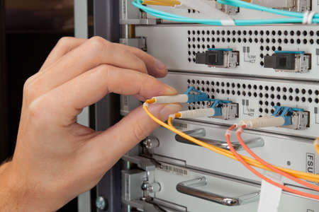 debugging: Network engineer insert patch cord in network hardware Stock Photo