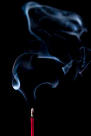 Blue smoke from the incense red stick on a black background photo