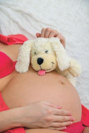 life giving birth: juguete suave en el est�mago de una ni�a embarazada en la ropa interior roja