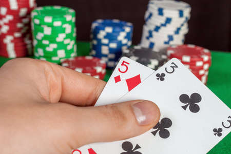 failure in poker, a bad card in hand; bluff; chips in the background