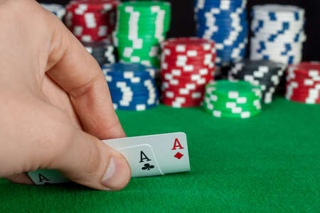 card player: Card player checks his hand, two aces in, chips in background on green playing table, focus on card