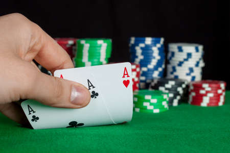 Card player checks his hand, two aces in, chips in background on green playing table, focus on card