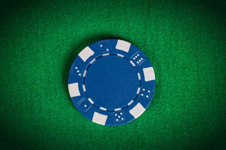 one vignette macro blue poker chip on green table
